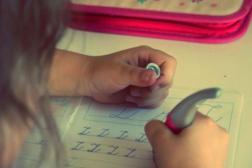 Free photo: The child writes homework