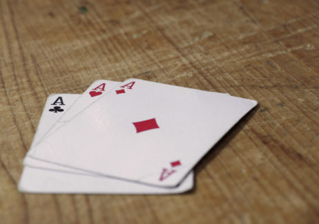 Three Aces Cards On Wooden Table