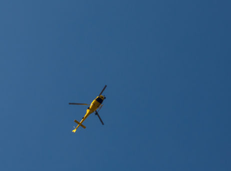 Yellow helicopter against the blue sky