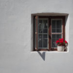 Vintage window with red roses white wall