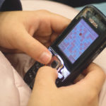 Young Girl Playing Sudoku On Old Mobile Phone