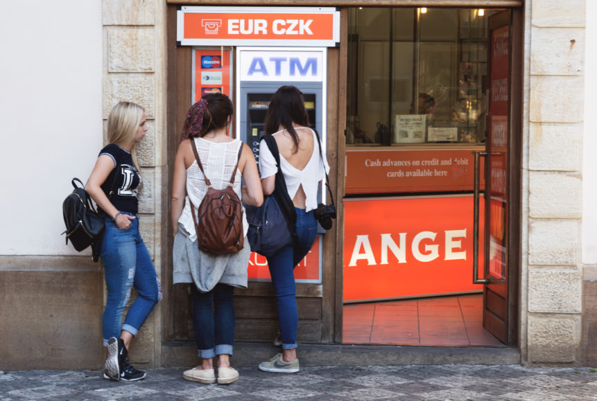 Three young women and atm