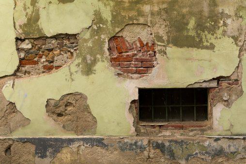 Grungy house facade with cellar window
